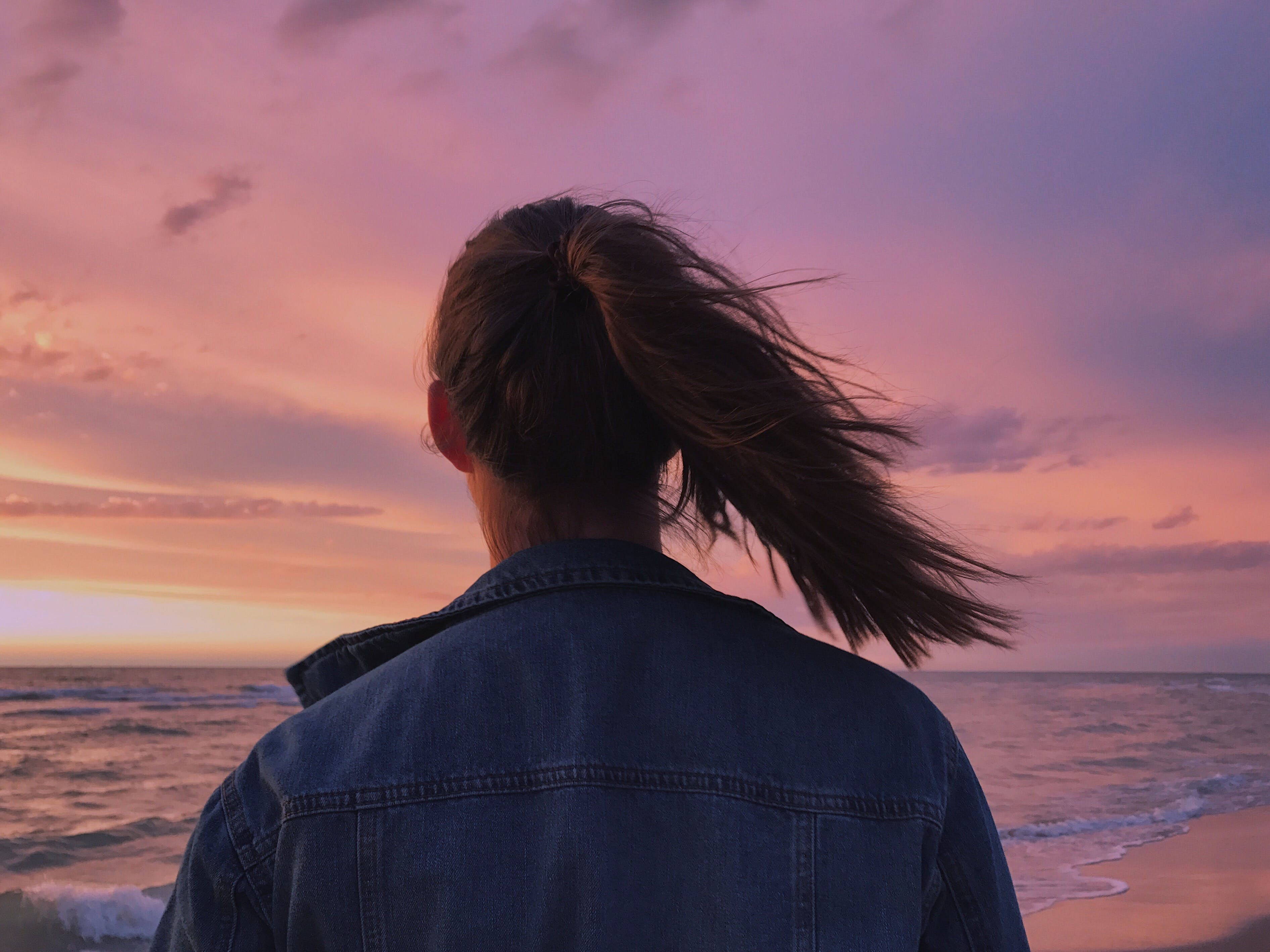 Woman Wearing Blue Denim Jacket Looking At The Beach
