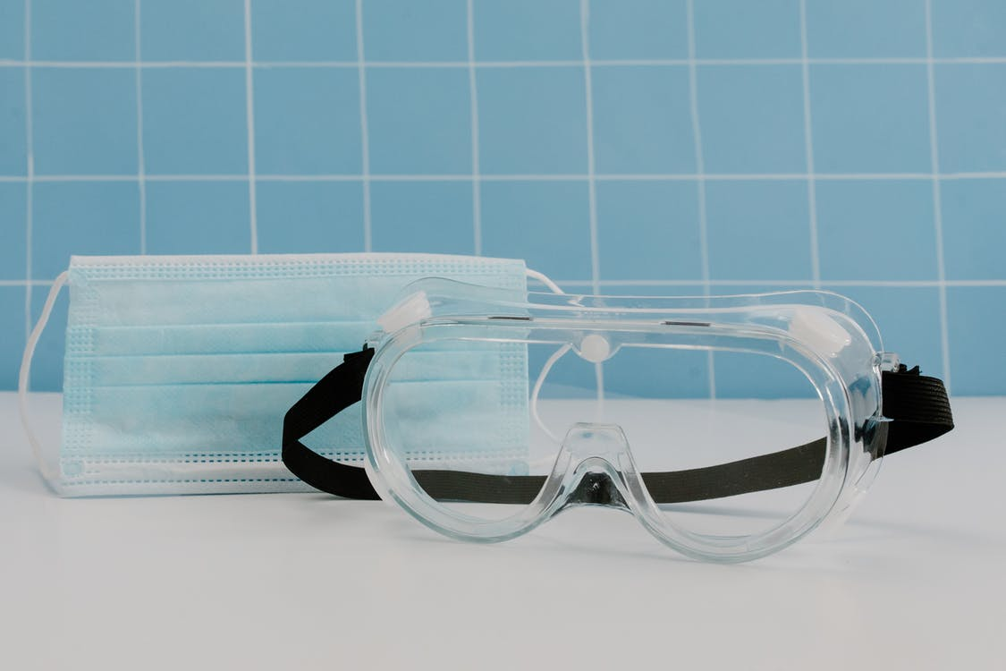 Close Up Photo of Disposable Facemask and Protective Goggles