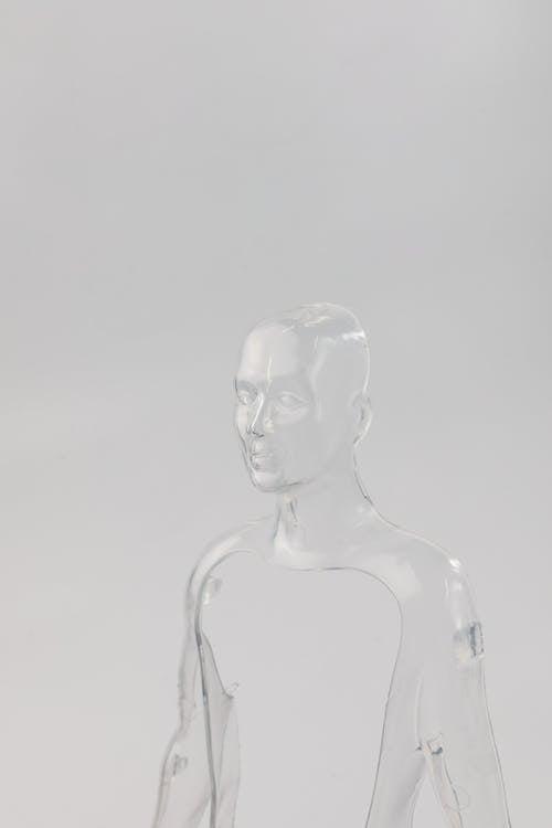 Clear Glass Buddha Figurine on White Surface