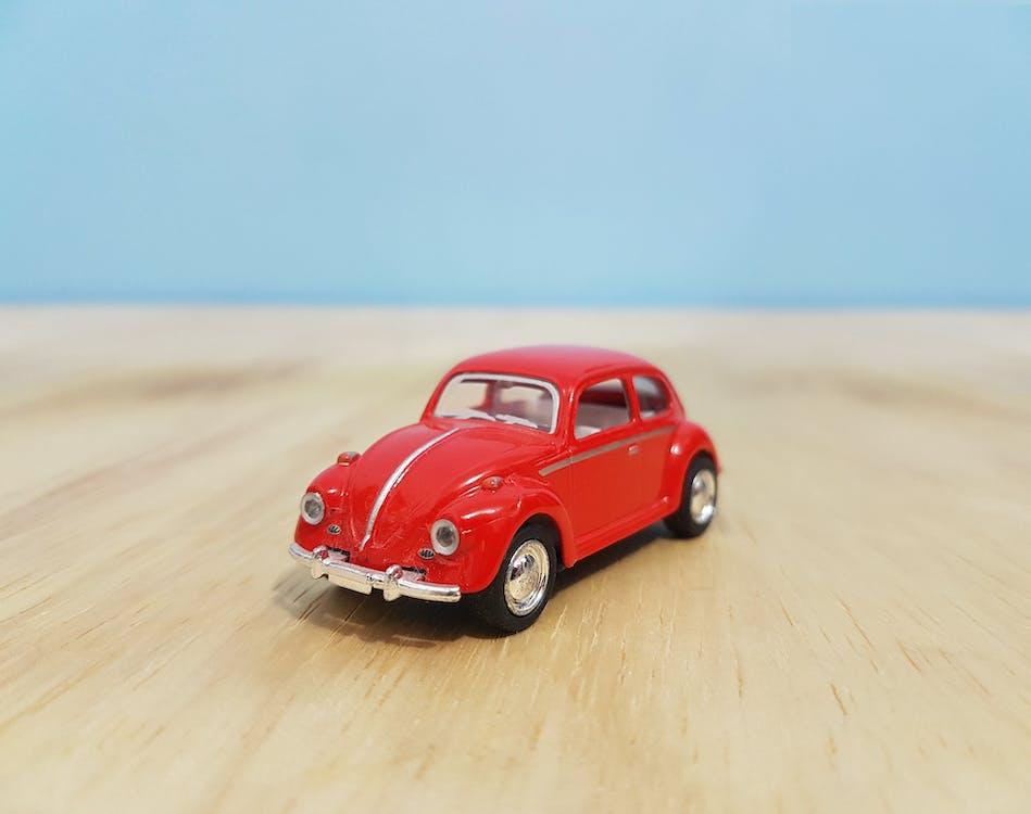 Depth of Field Photography of Red Volkswagen Beetle Diecast Model