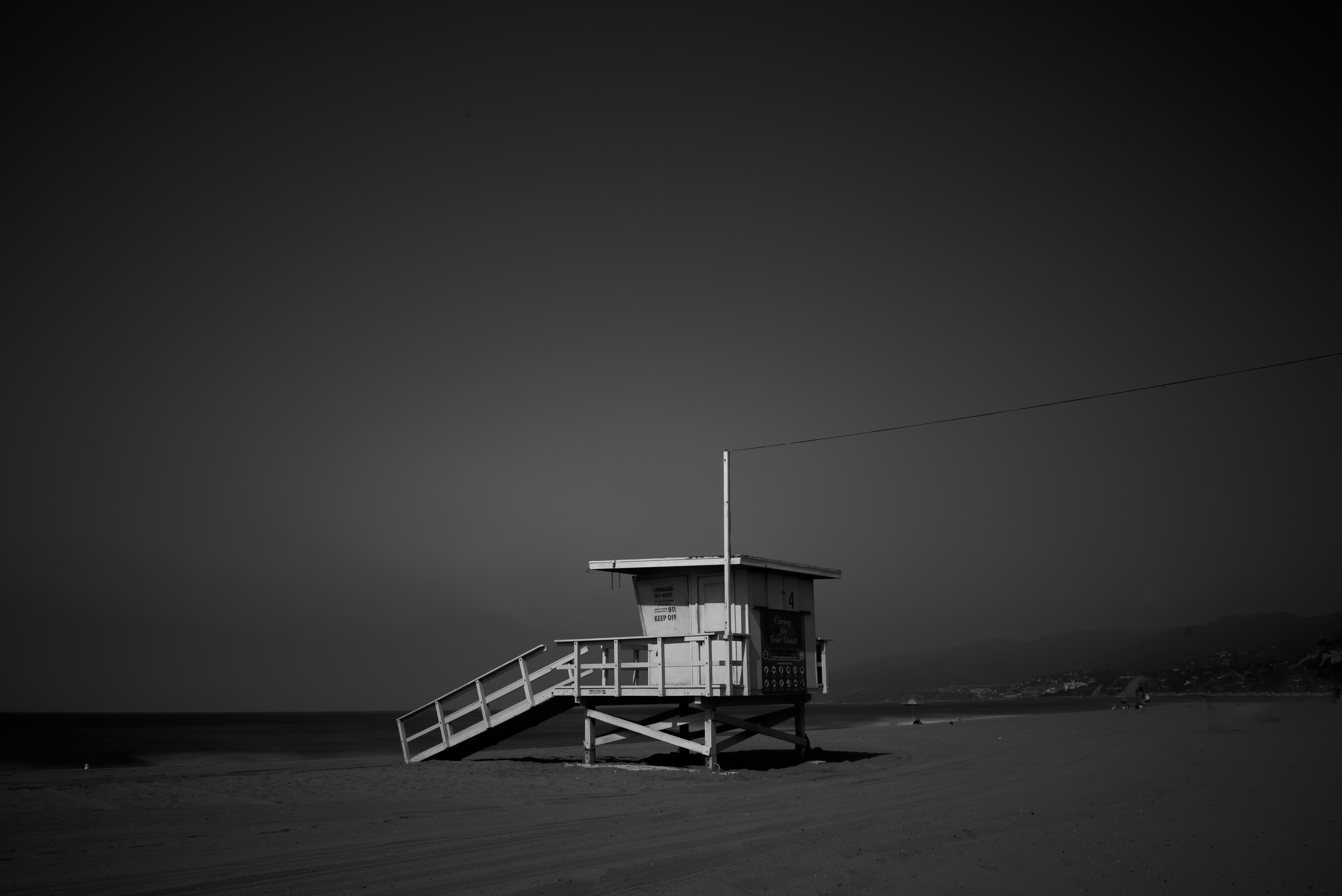 White Wooden Lifeguard House Near Shoreline