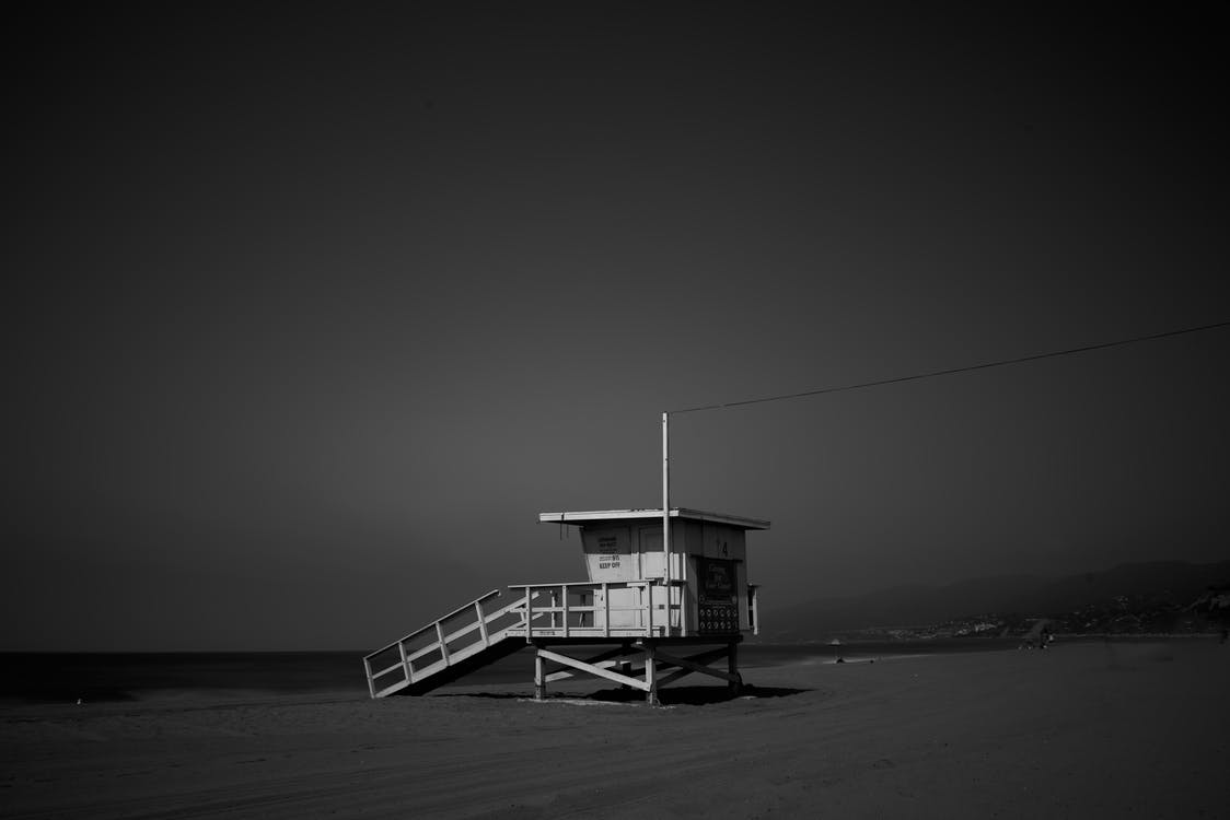 White Wooden Lifeguard House Near Shoreline