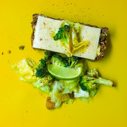 Photo of Green Broccoli, White Cheese and Green Cabbage on Yellow Surface