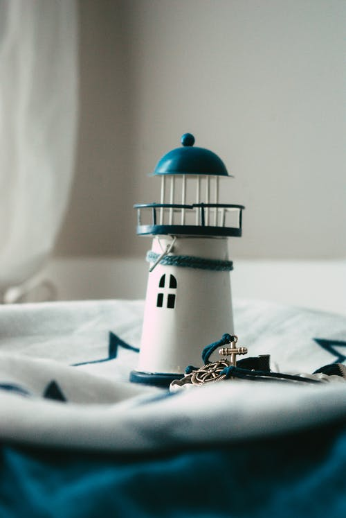 Small decorative lighthouse with blue elements placed on light fabric surface in room in daytime