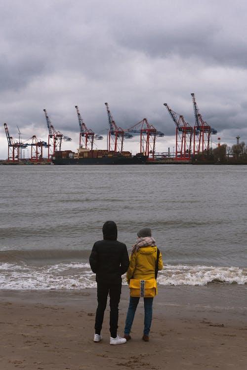 2 Men in Yellow Jacket Standing on Seashore
