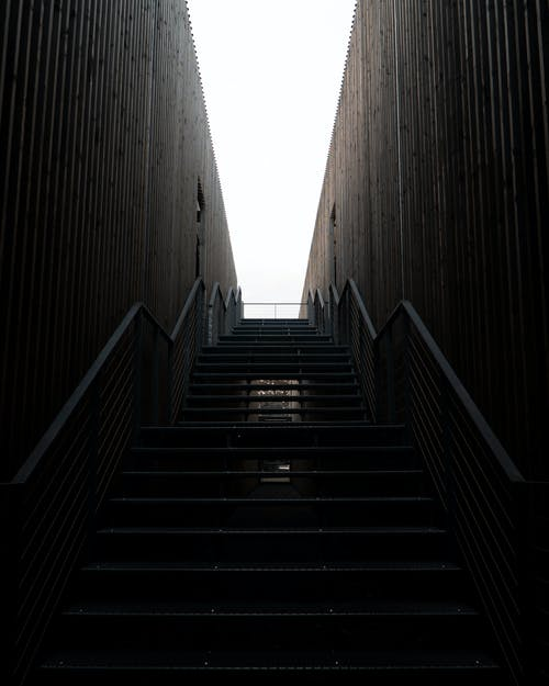 Brown Wooden Staircase Between Gray Concrete Walls