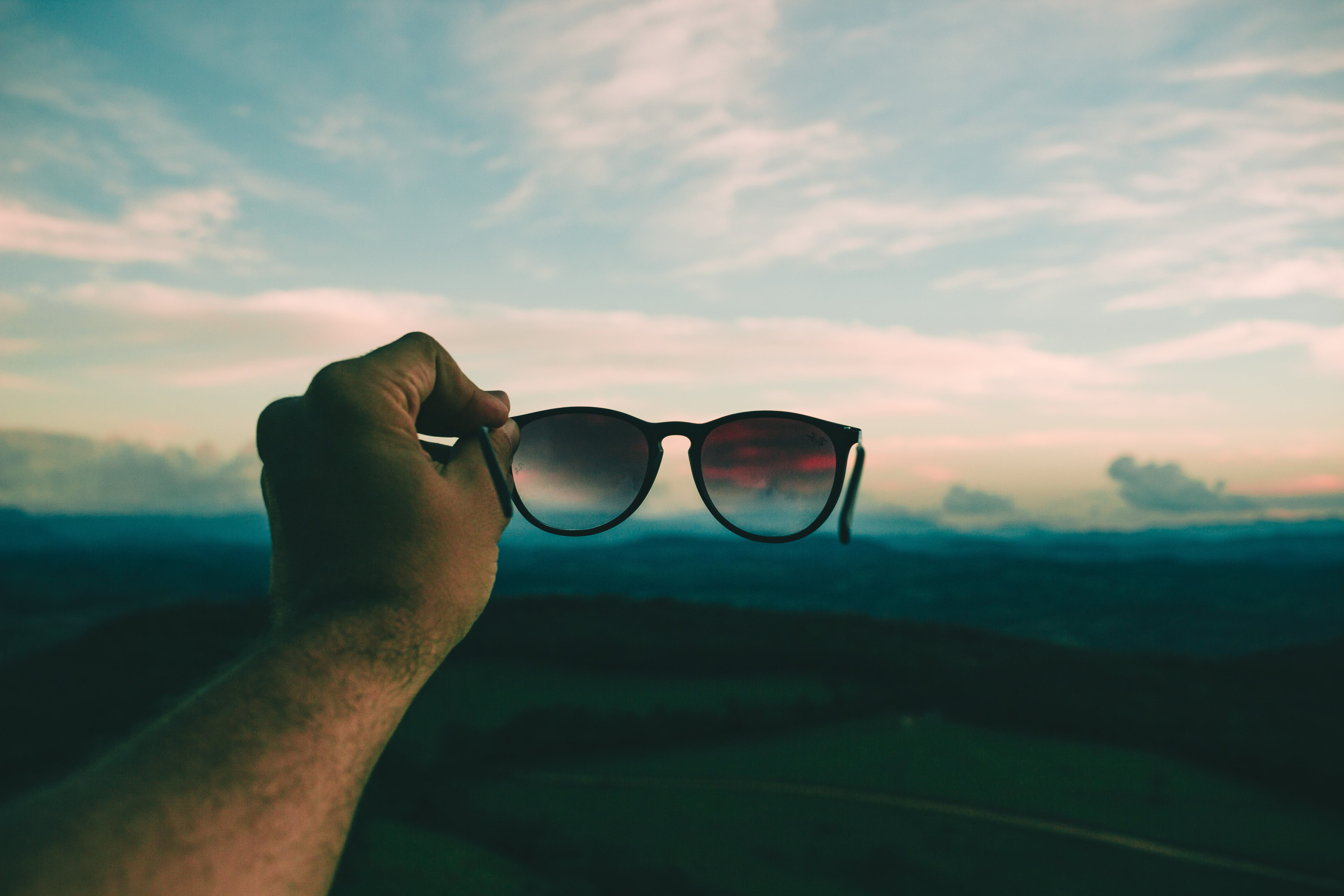 Person Holding Black Framed Sunglasses Under Blue Sky and White Clouds