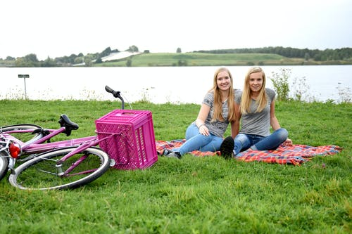 2 Women Lying on Green Grass Field Beside Pink and Black Stroller