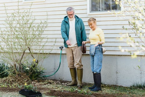 Full length of glad aged couple in rubber boots standing near house wall and looking at greenery on ground