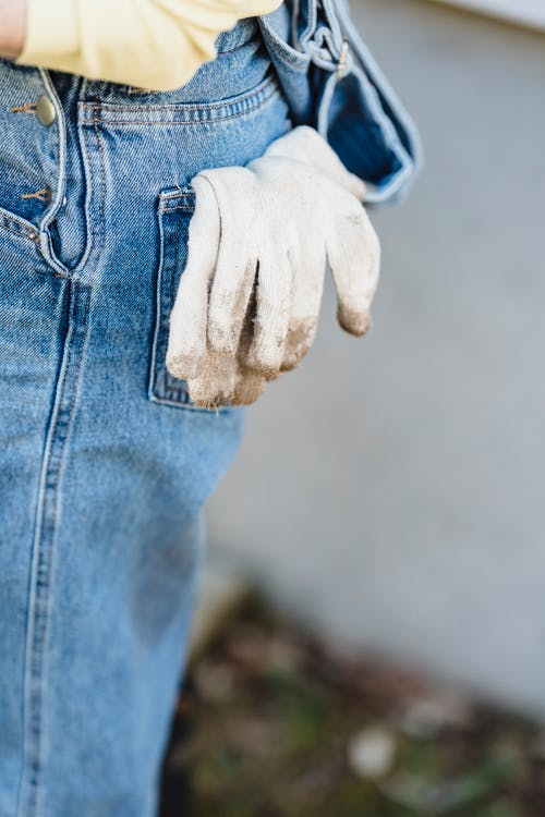 Dirty white gloves in back pocket of crop faceless person jeans on blurred background