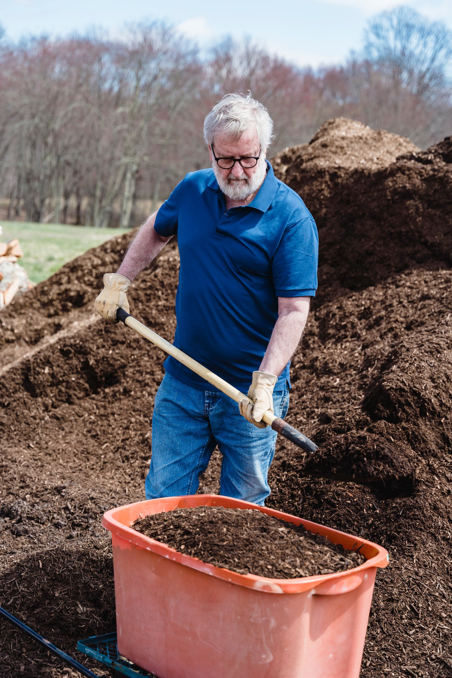 Man in Blue Polo Shirt Holding Brown Wooden Shovel