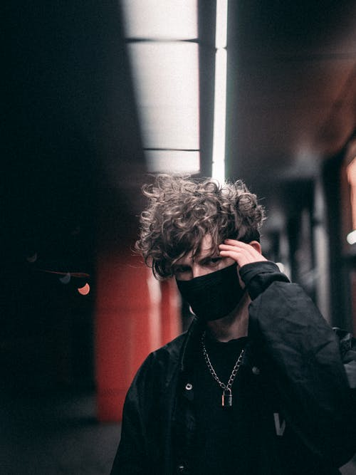 Young male with curly hair in black outfit and protective mask touching hair while standing on street near building and looking at camera at night