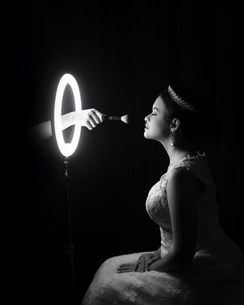 Side view of black and white unrecognizable beautician applying makeup on face of gorgeous bride in elegant dress and tiara sitting in dark room in front of round illuminated mirror
