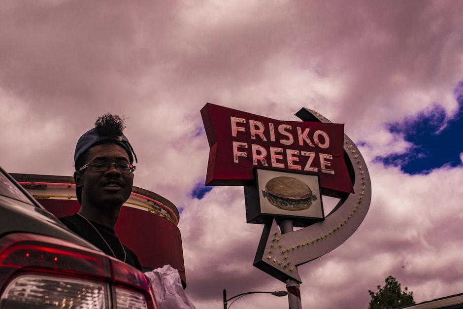 Man In Baseball Cap Near Frisko Freeze Signage