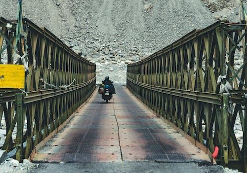 Person in Black Jacket and Black Pants Walking on Brown Wooden Bridge
