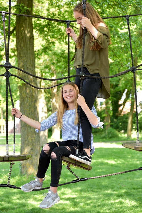 Woman in White and Black Striped Long Sleeve Shirt Sitting on Swing