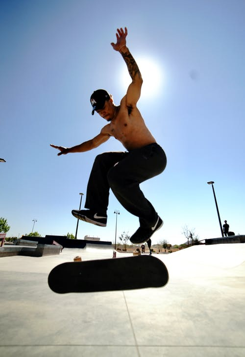 Man in Black Pants and Black Shoes Riding Skateboard