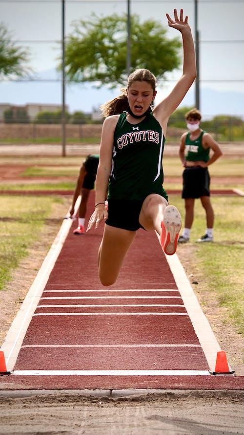 Woman in Black Tank Top Running on Track Field