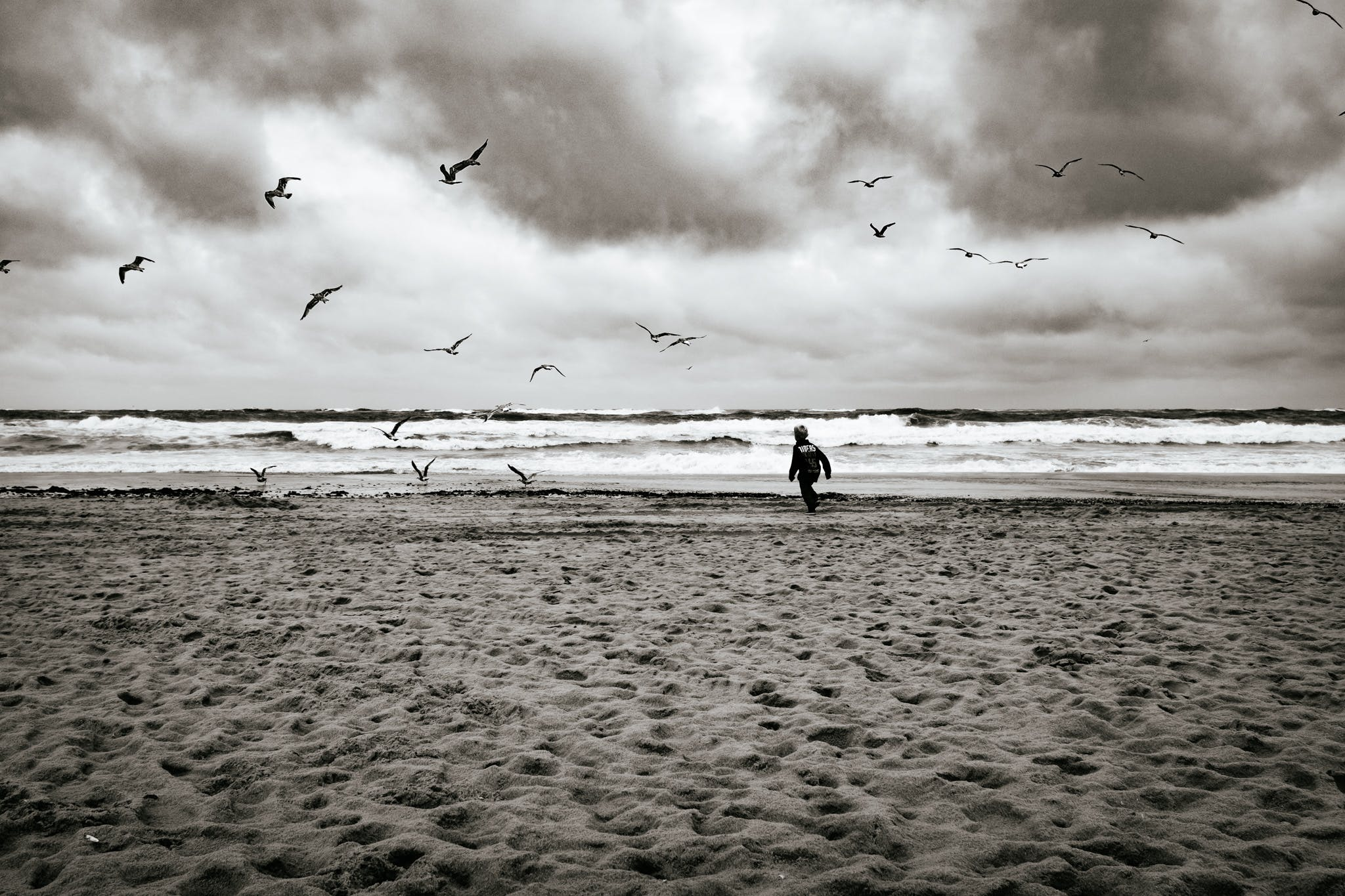 Grayscale Photography of Boy Running Near Sea