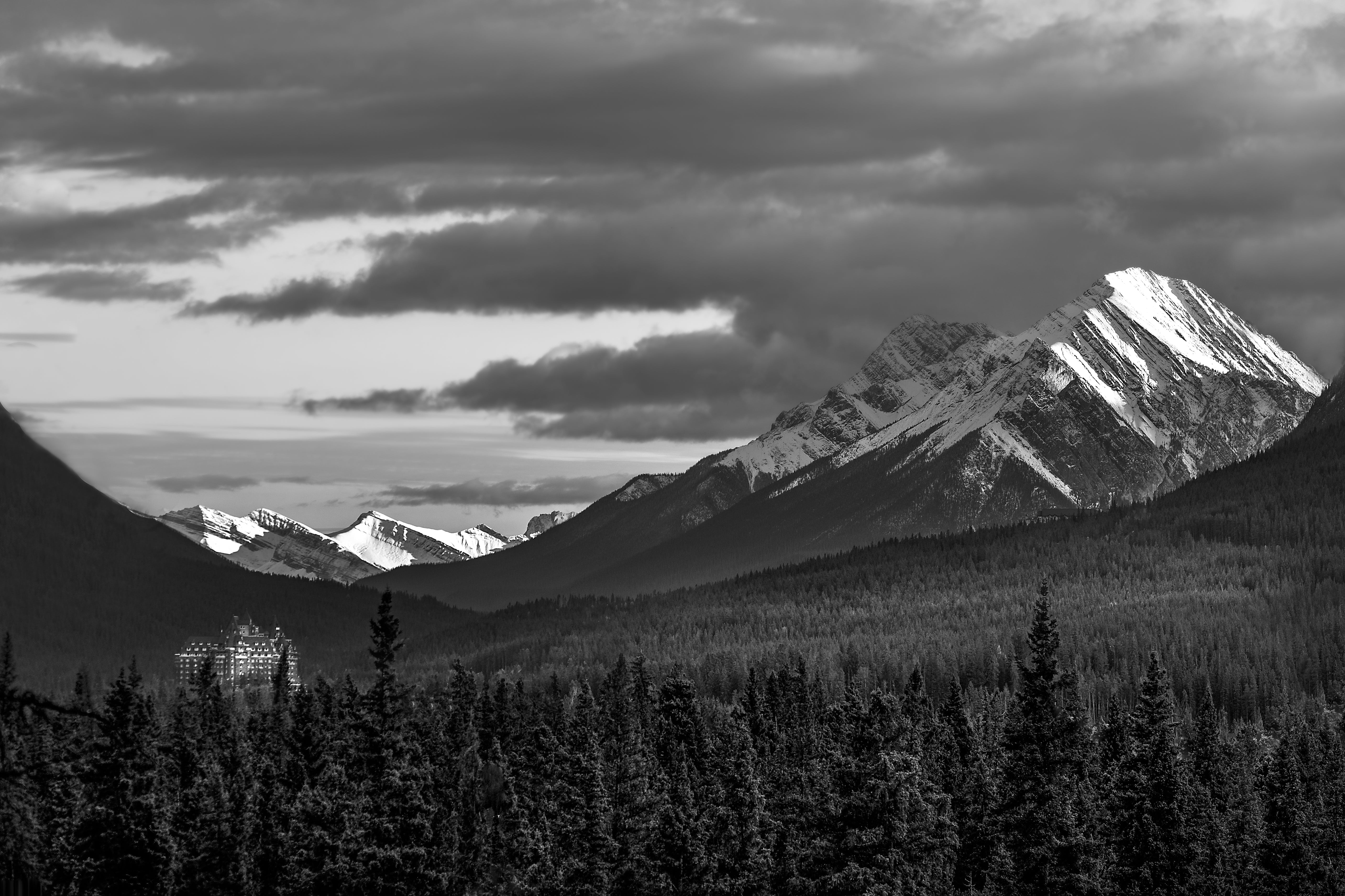 Grayscale Photography Of Snow Covered Mountain Under Cloudy Sky
