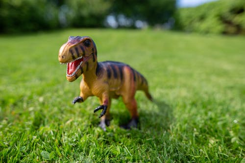 Close-Up Photo of a Dinosaur Figurine on the Grass