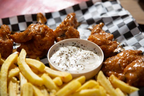 Close-up Photo of French Fries and Fried Chicken Wings