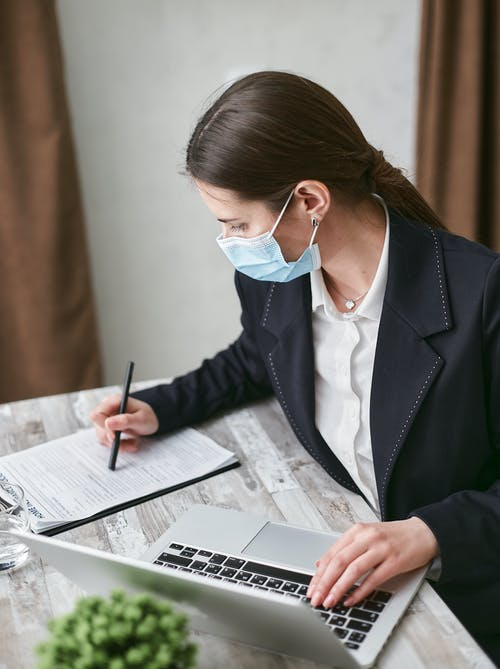 Woman in Black Blazer Using a Laptop