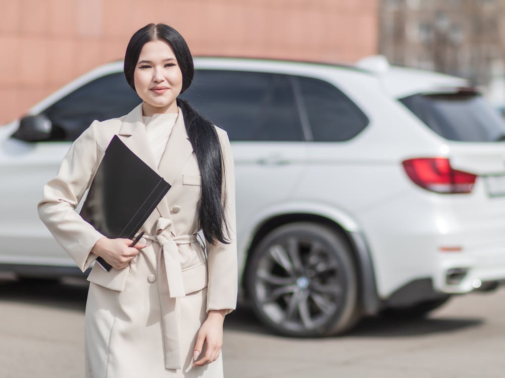Woman in Beige Corporate Clothes Holding Black Folder