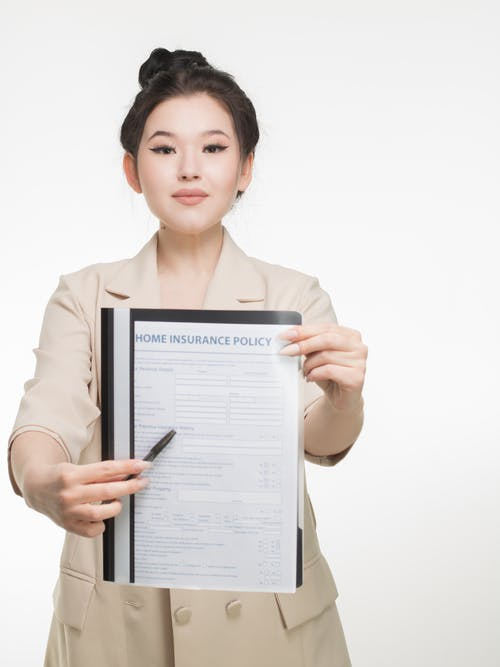 Woman in Corporate Attire Holding A Home Insurance Policy