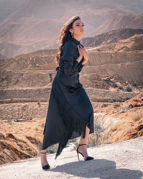 Woman in Black Dress Standing on Brown Field