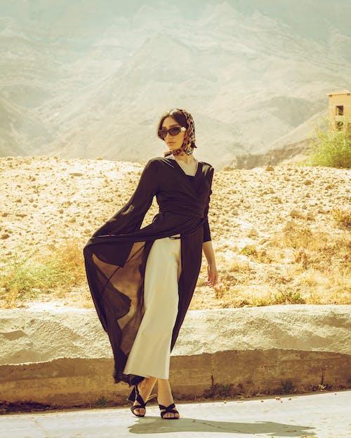 Woman in Black Long Sleeve Dress Standing on Brown Rock
