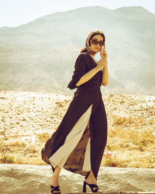 Woman in Black Dress Wearing Sunglasses Standing on Brown Field