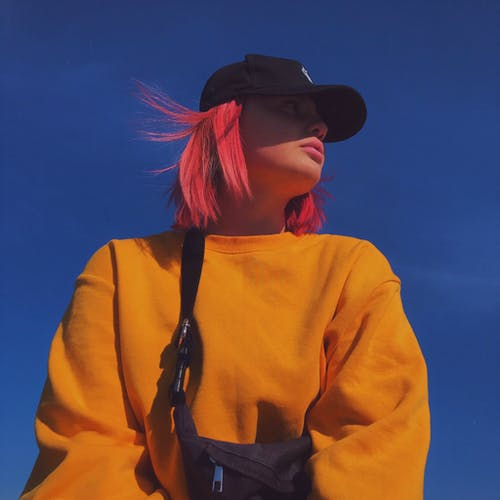 Woman With Colored Hair Wearing Yellow Long Sleeve Shirt And Black Cap