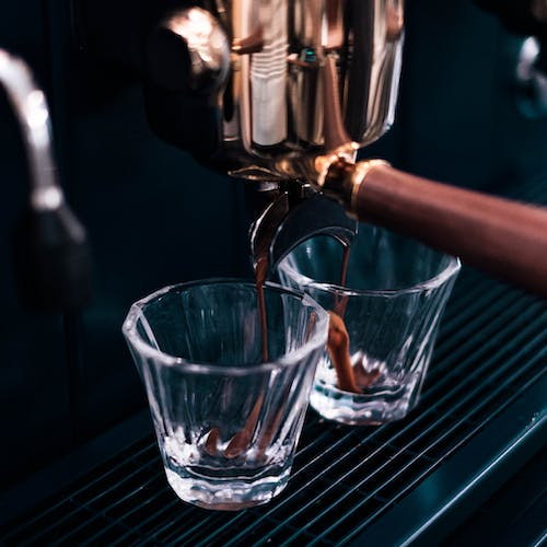 From above of coffee machine pouring tasty fresh aromatic espresso in to glasses in kitchen of cafe