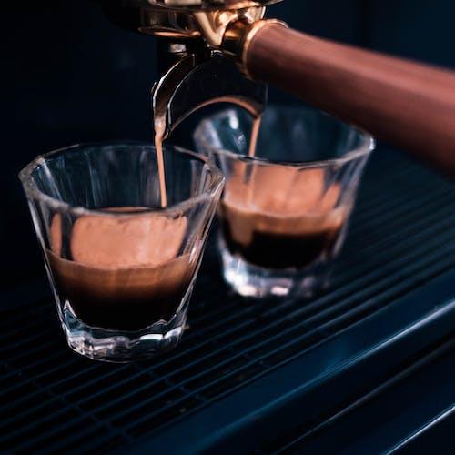 Modern coffee machine pouring espresso in glasses