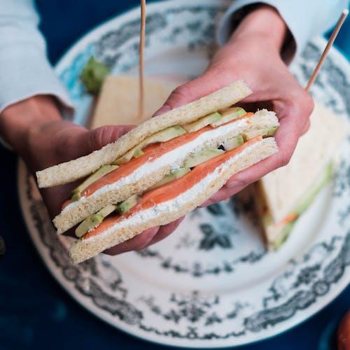 Person showing tasty fish sandwich in restaurant