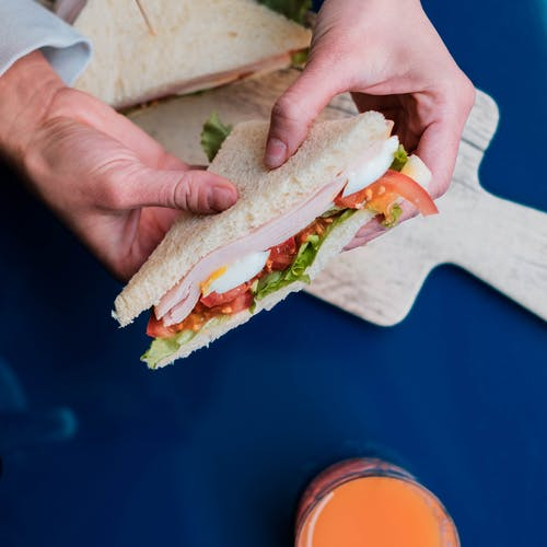 Person showing delicious sandwich with piece of tomato