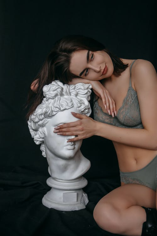 A Woman Leaning on a Bust while Wearing a Lingerie