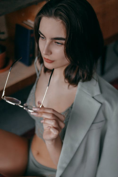 A Woman Holding Her Eyeglasses while Wearing a Blazer over a Lingerie