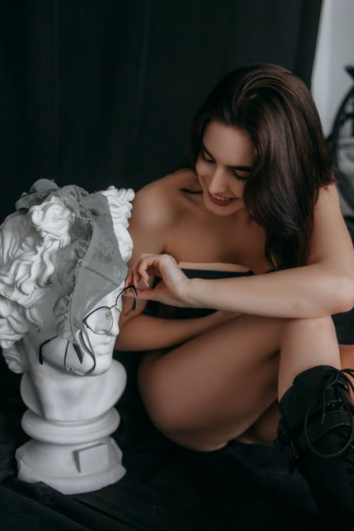 A Topless Woman Putting Eyeglasses on a Bust