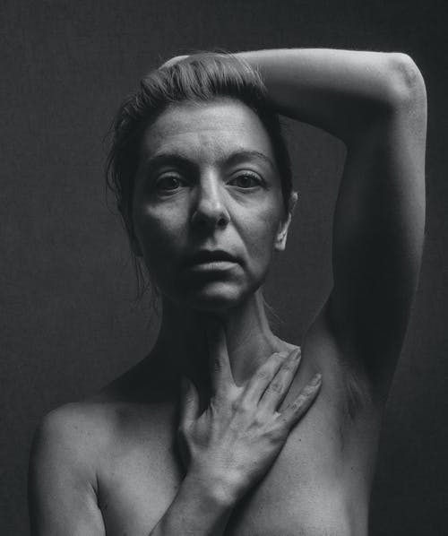 Grayscale Photo of a Topless Woman Posing at The Camera