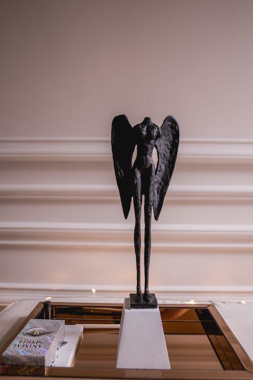 Black Headless Angel Figurine on White Pedestal
