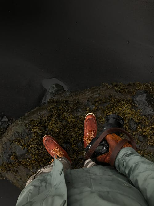 Person in Gray Pants and Hiking Shoes Standing on Rocky Cliff