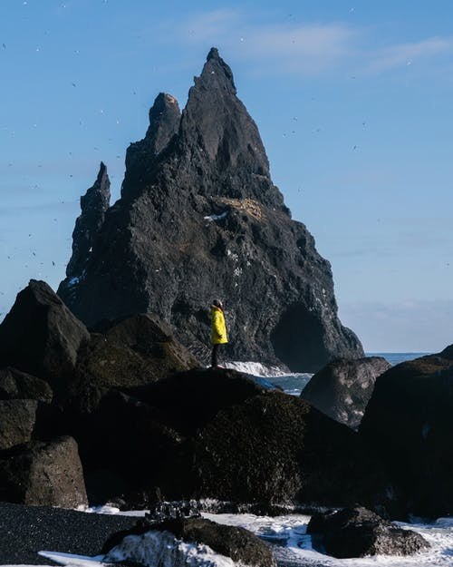 Person in Yellow Shirt Standing on Rocky Mountain
