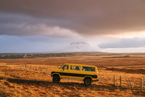 Brown and Black Suv on Brown Field Under White Clouds