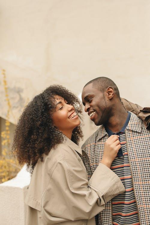 Man in Plaid Jacket Beside Woman in Brown Coat