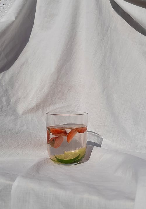 Clear Drinking Glass with Slices of Lime and Red Fruit in Water