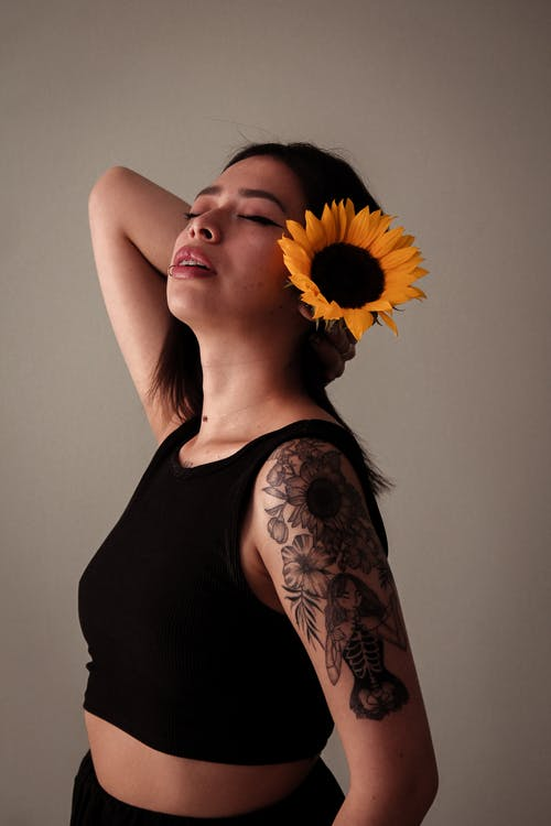 Woman With Sunflower on Her Ear Touching The Back of Her Neck