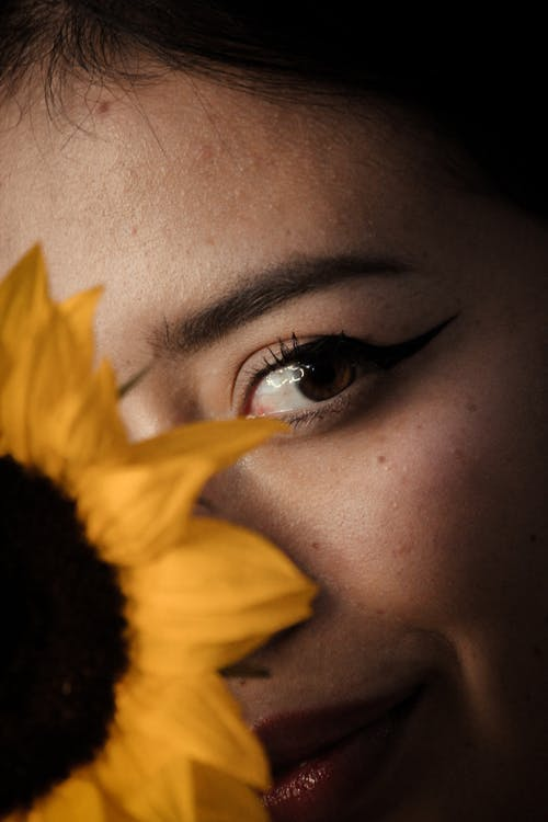 Sunflower Covering Half of The Face of a Woman With Eyeliner