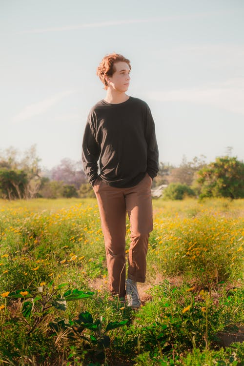 Man in Black Long Sleeve Shirt Standing on Green Grass Field